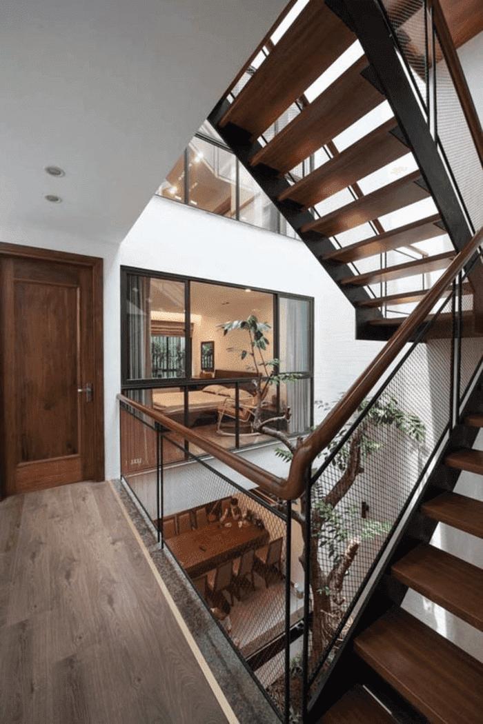 Giếng trời kết hợp với cầu thang khung thép bậc gỗ lan can kính.