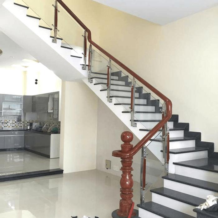 Mẫu cầu thang đẹp trong phòng khách sử dụng cầu thang kính tay vịn gỗ.