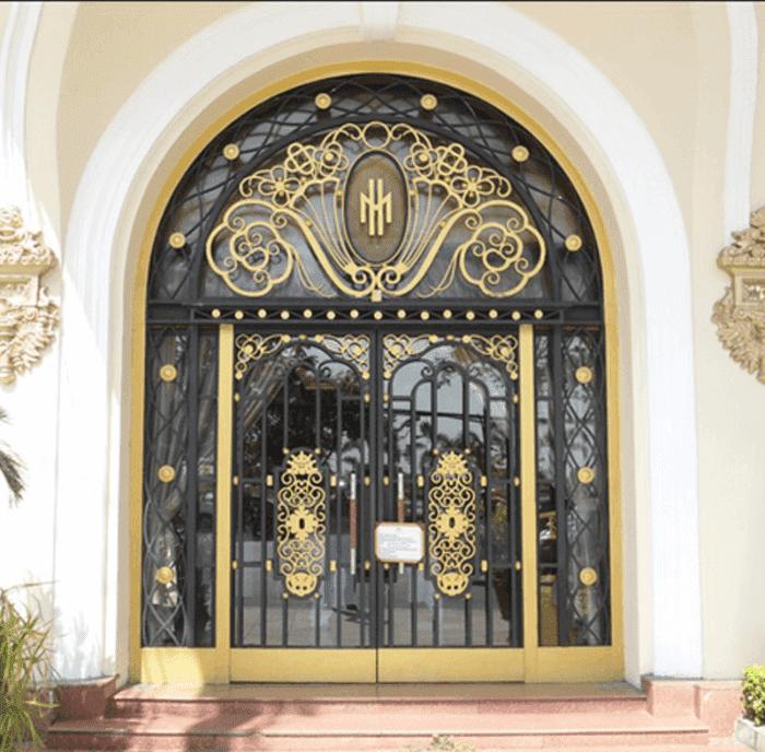 Lớp cửa sắt mỹ thuật đẹp ở ngoài, bên trong là cửa kính bản lề sàn.