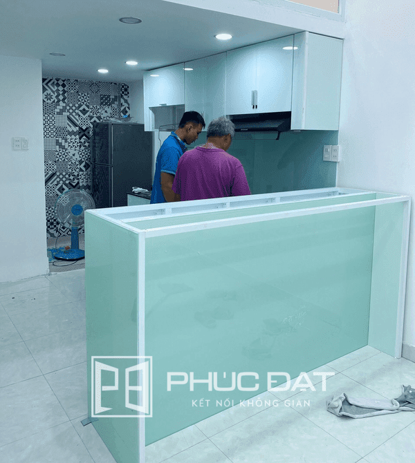 Tủ bếp kết hợp quầy bar sử dụng màu kính sơn trang nhã và tinh tế.