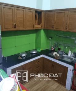 Tủ bếp kết hợp kính bếp màu xanh lá.