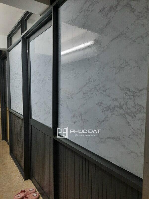 Vách nhôm kính phòng ngủ sử dụng kính dán phim giả đá sang trọng.
