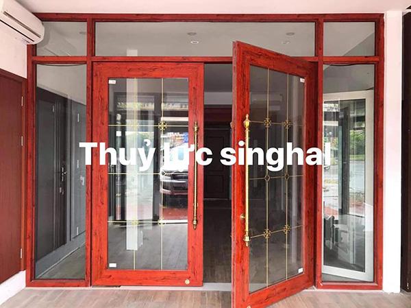Cửa khung nhôm kính cường lực hệ nhôm Singhal màu giả gỗ.
